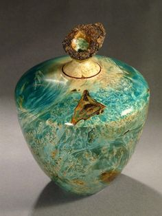 """Ray Asselin, Wilbraham, MA - """"The Bermuda Triangle"""", Dyed Boxelder Burl Hollow Vessel, 8-1/4 x 6 inches. Reminds me of scenes from space, looking down on the earth... atmosphere and ocean swirls. The dark triangular bark inclusion suggested the name."""