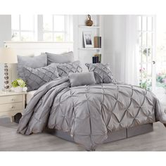 The free flowing pin-tuck pattern of this stunning comforter set covers the whole comforter and the shams, giving you a complete look from head to toe. Available in grey, light blue or white, this set is sure to give your room a makeover.