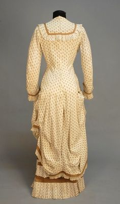 Printed cotton Polonaise dress, cream with repeat of brown grape clusters, unboned pannier bodice with pleated ruffle to yoke and cuff, brown trim bands, back buttons, lace hem trim, under skirt with double row of hem pleats, 1880's.