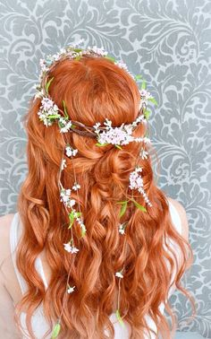 This warm red hair color pops against the light floral crown.
