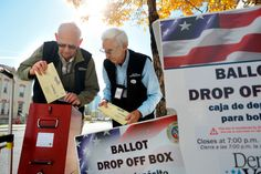 In this file photo, election judges transfer ballots from a drop box outside of the library on October 22, 2012 in Denver.