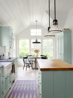 Instead of going the traditional route with wood cabinets, this Connecticut Farmhouse opted for mint cabinetry. A geometric rug in similar pastel hues adds the perfect finishing touch.