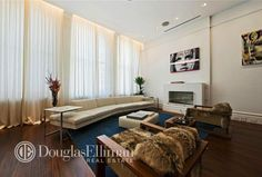 This NYC living room has wood floors, blue area rug, furry arm chairs, a fireplace, sheer curtains and high ceilings.