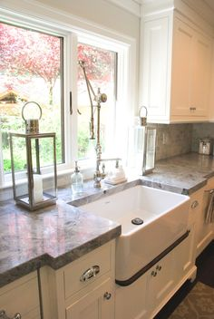 Farmhouse sink with drip edge underneath, furniture style white cabinets, large kitchen window, Super White quartzite countertops. The Granite Gurus: Carrara Marble & Super White Quartzite Kitchen from MGS by Design