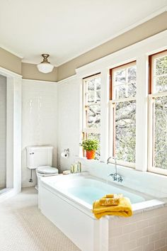 Oversize windows in this bathroom on the facing wall deliver not only daylight but also leafy tubside views.