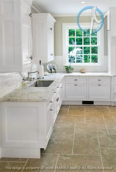 This classic white kitchen is spacious, bright, and very inviting. The darker tile adds the needed contrast and compliment the Bianco Romano countertops.