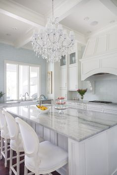 Sea pearl quartzite - similar color to carrera The kitchen island is topped with Sea Pearl Quartzite that picks up the blue tint of the glass tile backsplash, while the paneled detailing on the cabinets is carried through to the Thermadore exhaust hood. The casement window opens onto the outdoor kitchen so that things can be passed through with ease when entertaining. Chairs from Restoration Hardware.