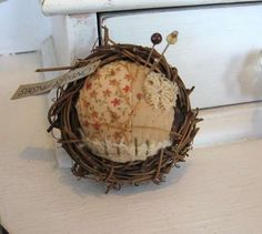 "This tiny little bird nest pincushion is as light as a feather. A delightful addition to a shadow box or collection, it has a little bit of everything. Patchwork and embroidery depicts a tiny little country scene on a sunny day. Sewn together using cotton, linen and love, the story is of a vine rising to the sun just beyond the garden gate. Only about 1 1/2""."