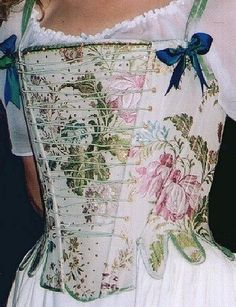 A highly decorative eighteenth  century style corset / stays in a brocade fabric, lined and bound in silk  dupion with false front lacing, silk bound tabs and a beaded stomacher.Fully  boned; laced at the back and shoulder.