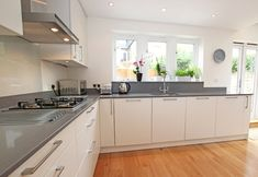 German satin lacquer kitchen design. Open plan kitchen arrangement with Compac Quartz worktop.