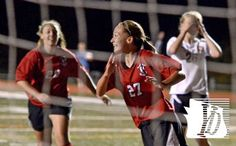 Dover's Paige Hartman, center, reacts after scoring the Eagles' third goal against Northeastern, Tuesday October 8, 2013. John A. Pavoncello...