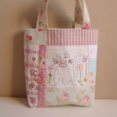 I think you will like this...Surprise!  Cute little kitty on a dainty little tote bag!  It's all pretty and pink too!