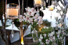 Flores e velas penduradas em árvores.