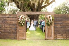 reclaimed doors and plank walls serve as entry to this outdoor wedding under the oak trees. Loose and wild flowers and greenery adorn the weathered doors.