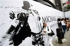 Fans sign a mural of Michael Jackson outside the Staples Center where the public memorial for Jackson is being held in Los Angeles, California, U.S. on Tuesday, July 7, 2009. Los Angeles officials are preparing for half a million Michael Jackson fans and mourners to converge downtown for today's memorial tribute to the singer, capping almost two weeks of global frenzy over the 'King of Pop.'