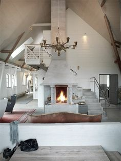 Stairs wrapped around this fireplace which keeps a traditional Swedish Skånelänge warm.