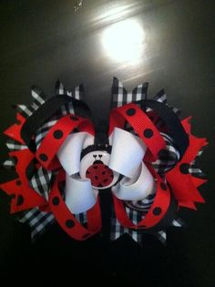 I like this ladybug bow, but with a red/white checker, not black/white, more like a picnic table cloth