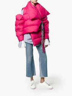 This pink Marques Almeida oversized asymmetric puffer jacket on one hand will make your Granny Mildred proud for it'll keep you warm during the cooler months, however on the other hand, we're not too sure what she'll think of the shape and right cold shoulder. It may be a bit avant garde for her tastes but not for ours. The result of impeccable workmanship, this pink puffer jacket boasts an oversized collar, front blue and white gingham tie closure, long sleeves and an asymmetric hemline…
