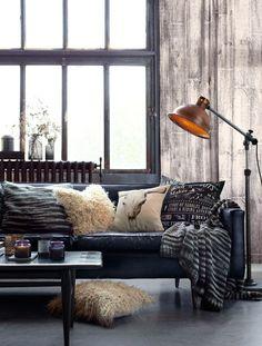 decoração sala de estar no estilo industrial com sofá de couro azula, parede rústica de concreto, luminária de chão