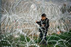 Un niño observa el otro lado de la frontera tras una concertina en la frontera de Grecia con Macedonia.