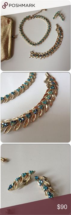 """SIGNED CORO VINTAGE PARURE AB CRYSTALS & GOLD Signed Coro vintage green/blue AB crystals flanked by gold detailed leaves. The set is in perfect condition with crystals intact. Bracelet & necklace are articulated. The bracelet has fold over clasp & safety chain measures 7"""". Necklace has hook & chain closure measures 12"""" & 3"""" extension chain. The earrings are 1.5"""" long clip ons. The color of the crystals reflected in the gold leaves, is a beautiful thing! This is a lovely set of vintage Coro…"""