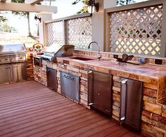 Equipped with a sink and garbage disposal, a refrigerator, ice maker, trash compactor, three types of grills, and a power burner, the outdoor kitchen is efficient, flexible, and ideal for any size gathering. Sconces and backsplash lighting provide ambient and task illumination.