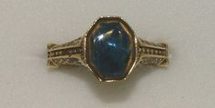 14th Century: Ring  Gold ring, the transverse octagonal bezel set with a table-cut sapphire in a channeled collet, the openwork hoop, formerly enameled, interspersed with three knots of Hercules, each enclosing a star between a line of pellets