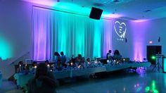 20 foot lighted backdrop with teal and purple wireless led uplighting and gobo projection. Www.orlandodjandlighting.com