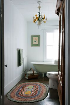 vintage bathroom with claw foot tub and braided rug