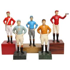 Group of iron lawn jockey sculptures on wooden pedestals in various colours, each wearing their colourful signature silks, USA c. 1920