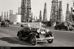 Los Angeles, California - 1930s: oil derricks alongside a main highway during the oil boom.