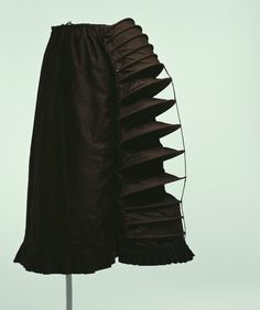 Bustle - c.1870s. Material: Brown cotton satin with fifteen metal wires placed at back; black silk taffeta pleats at lower back.