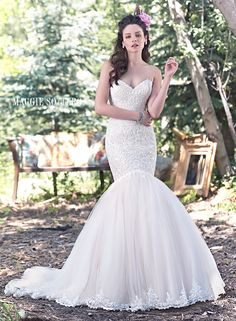 Lansing wedding dress by Maggie Sottero | Exquisite lace hugs the bodice of this romantic fit and flare wedding dress, before falling into a dramatic tulle skirt, edged in delicate lace. Finished with sweetheart neckline and corset closure.