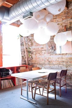 Paper lanterns: various sizes.... no more than 3 hanging in the corner near round table?  Frees up floor space but softens lines.