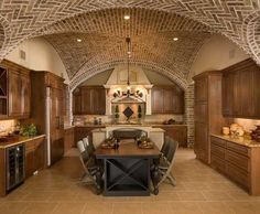 A kitchen featuring brick groin vault ceilings and stained wood cabinetry. What do you think of the brick ceiling? Design by http://www.csceilings.ca/