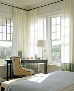 Chic bedroom boasts corner desk with a camel linen chair placed under windows dressed in green banded drapery panels.