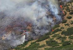 Trees go up in flames as a helicopter drops water on the Quail Fire in Alpine, Utah, July 3, 2012. The fire started this afternoon and spread quickly through the eastern end of Alpine and then up the mountain side. It is still out of control.