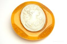 This amazing vintage Art Deco pin brooch features a beautiful ivory color celluloid cameo nestled in a carved butterscotch Bakelite frame. There