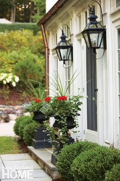 Landscape designer Jeff Stevens and interior designer Karen Quinn turned what was once a dairy room into an inviting entry space. Urns of geraniums and a crisp hedge of Winter Gem boxwood provide the initial welcome.