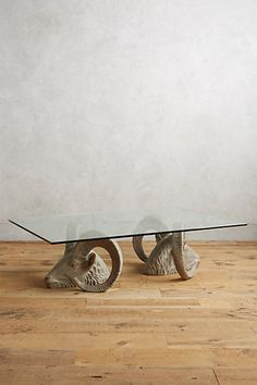 Land & Sky Coffee Table - Traditionally symbols of determination, these rams are rendered in intricately carved resin. They face outward in a show of strength as their curved horns support a clear glass top.