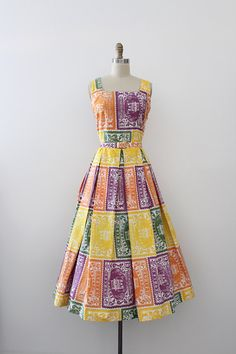 Gorgeous novelty dress from the 1950s. This dress features a vibrant bold novelty print of foreign stamps, a fitted waistline with matching belt,