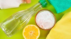 Baking soda sitting in a glass bowl surrounded by sponges, half a lemon and an empty bottle