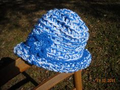 Orginial Crocheted Triple Strand Hat made with Dark Blue White and Baby Blue with Silver strands topped off with a flower. Machine Washable (lay