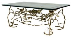 1950s solid brass and glass midcentury coffee table in the style of Diego Giacometti. Its natural bird and branch motif is extremely detailed; thick beveled glass top.Driven by their passion for...
