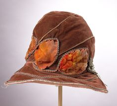 1920s brown silk velvet cloche with a 3-inch wide brim that disappears to a quarter of an inch at the center back. The hat is decorated with braided trim in orange blue and gold. An iridescent green ribbon accents the sides of the hat. Three umbra velvet leaves accent the front of the hat. Velvet leaves are circled by the matching orange gold and blue trim. Gold lame piping separates the sections of the tall crown.