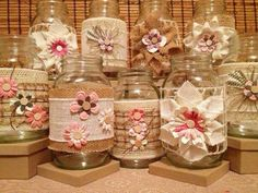 Mason jars decorated with fabric flowers and burlap.