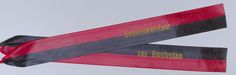 Anonymous | Lint van het gemeentebestuur Amsterdam, Anonymous, 2000 | 2 Linten van het gemeentebestuur Amsterdam, gelegd op 4 mei 2000 bij het Nationaal Monument op de Dam. Beide linten zijn verdeeld in twee horizontale banen. Op het midden een gouden opdruk. Beide aan een zijde gebonden met ijzerdraad om een houten rond stokje ter bevestiging in een krans. Andere uiteinde voorzien van een kartelrand. A-1: bovenzijde rood, onderzijde zwart. A-2: bovenzijde zwart, onderzijde rood (stokje…