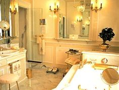Coco Chanels bathroom. Note gold fittings, gold monogrammed towels, swing mirrors, footstool with renovated cover (!), the thing behind the bath...what is it? Bonsai?