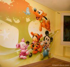 Quatre des personnages Disney sur fond graphique sur un mur d'une chambre de bébé