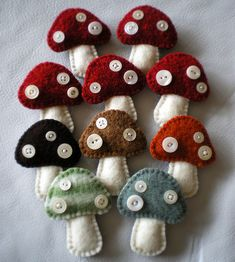 10 little wool toadstool brooches made of a combination of felted wool sweater and handmade wool felt. The spots are vintage mother of pearl buttons.